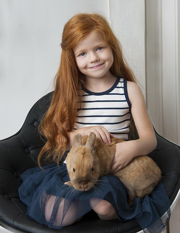 Kislány ül a széken kezében egy igazi nyuszival